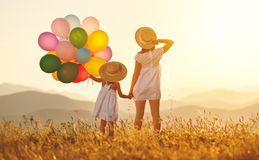 Happy family mother and child with balloons at sunset in summer Royalty Free Stock Images