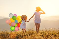 Happy family mother and child with balloons at sunset in summer royalty free stock photo