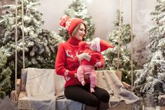 Happy family mother and child boy in santa hat near snow covered Christmas trees with sitting on swing. Bright garland. Happy family mother and child boy in Stock Images