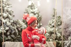 Happy family mother and child boy in santa hat near snow covered Christmas trees with sitting on swing. Bright garland. Above heads Royalty Free Stock Photo