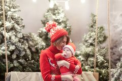 Happy family mother and child boy in santa hat near snow covered Christmas trees with sitting on swing. Bright garland. Above heads Royalty Free Stock Images