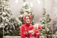 Happy family mother and child boy in santa hat near snow covered Christmas trees with sitting on swing. Bright garland. Above heads Stock Photos