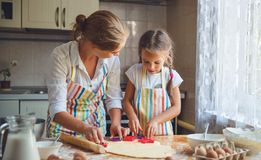 Happy family mother and daughter bake kneading dough in kitchen. Happy family mother and child daughter bake kneading dough in the kitchen Stock Image