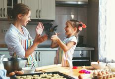 Happy family mother and daughter bake kneading dough in kitchen Stock Photos
