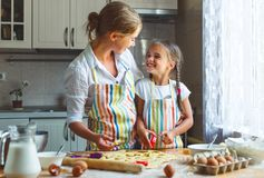 Happy family mother and daughter bake kneading dough in kitchen. Happy family mother and child daughter bake kneading dough in the kitchen royalty free stock image
