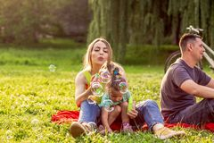 Happy family mother and child daughter blow soap bubbles royalty free stock photography
