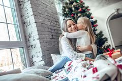 Happy family mother and child daughter on Christmas morning at the Christmas tree with gifts. Family, holidays and happiness concep royalty free stock image