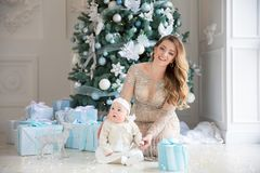 Happy family mother and child daughter on Christmas morning at the Christmas tree with gifts royalty free stock image