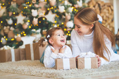 Happy family mother and child daughter on Christmas morning  tre. Happy family mother and child daughter on Christmas morning at the Christmas tree with gifts Royalty Free Stock Photo