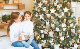 Happy family mother and child daughter on Christmas morning  tre Royalty Free Stock Photo