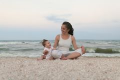 Happy family mother and child daughter doing yoga, meditate in lotus position on beach at sunset royalty free stock images
