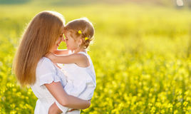 Happy family mother and child daughter embrace  on nature in sum. Happy family mother and child daughter embrace on yellow flowers on nature in summer Royalty Free Stock Images