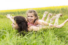 Happy family mother and child daughter embrace on yellow flowers on nature in summer. A Happy family mother and child daughter embrace on yellow flowers on Royalty Free Stock Images