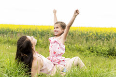 Happy family mother and child daughter embrace on yellow flowers on nature in summer Stock Photography