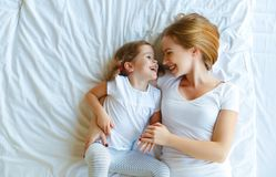 Happy family mother and child daughter laugh in bed Stock Photo