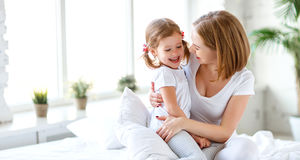 Happy family mother and child daughter laugh in bed. Happy family mother and child daughter play and laugh in bed Stock Photos