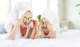 Happy family mother and child daughter make face skin  mask. With towel on head Stock Photos