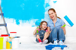 Happy family mother and child daughter making repairs, paint wal. Happy family mother and child daughter making repairs, paint the wall at home Royalty Free Stock Images