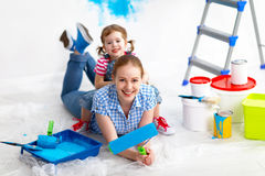 Happy family mother and child daughter making repairs, paint wal Royalty Free Stock Photos