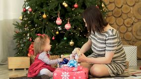 Happy family, mother and child daughter near decorated Christmas tree with gifts playing with toys. Beautiful, brunette royalty free stock photography