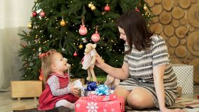 Happy family, mother and child daughter near decorated Christmas tree with gifts playing with toys. Beautiful, brunette stock photos