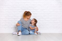 Happy family mother and child daughter near an empty wall Stock Image