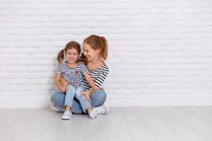 Happy family mother and child daughter near an empty wall Stock Images