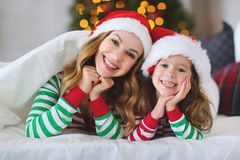 Happy family mother and child daughter in pajamas opening gifts stock photography