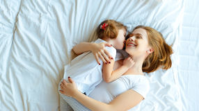 Happy family mother and child daughter laugh in bed. Happy family mother and child daughter play and laugh in bed Royalty Free Stock Image