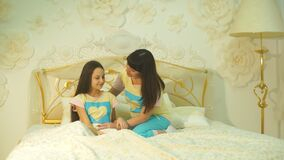 Happy family mother and child daughter play and laugh in bed stock video