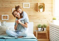 Happy family mother and child daughter laughing in bed Royalty Free Stock Photos