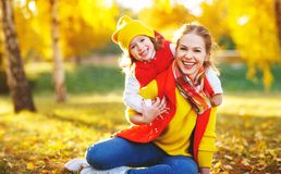 Happy family mother and child daughter on autumn walk. Happy family mother and child daughter playing and laughing on autumn walk royalty free stock images