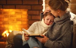 Happy family mother and child daughter read book on winter eveni. Happy family mother and child daughter read a book on winter autumn evening near fireplace stock image