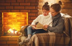 Happy family mother and child daughter read book on winter eveni. Happy family mother and child daughter read a book on winter autumn evening near fireplace Royalty Free Stock Image