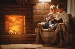 happy family mother and child daughter read book on winter evening near fireplace