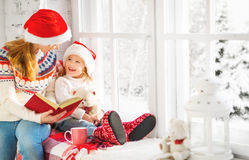 Happy family mother and child daughter reading book on winter wi Royalty Free Stock Image