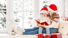 Happy family mother and child daughter reading book on winter wi Stock Photos