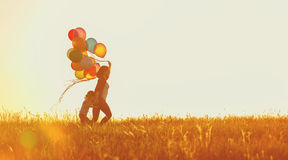Happy family mother and child daughter running with balloons on. Meadow in summer at sunset Stock Image