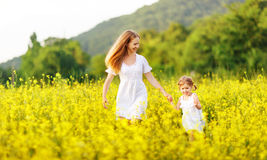 Happy family mother and child daughter running in  nature in sum. Happy family mother and child daughter running  in a meadow  yellow flowers on nature in summer Royalty Free Stock Image