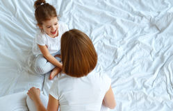 Happy family mother and child daughter talk in bed Stock Images