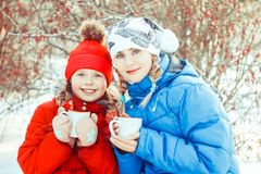 Mother and daughter drinking tea in winter. Happy family mother and child daughter on a winter walk outdoors drinking tea stock photos