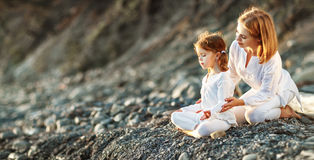 Happy family mother and child doing yoga, meditate in lotus position on beach stock photos