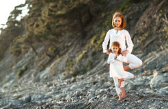 Happy family mother and child doing yoga, meditate in lotus posi Stock Photos