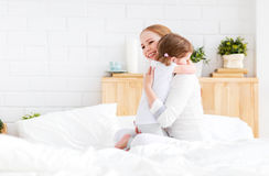 Happy family mother and child embracing huging in bed. Happy family mother and child daughter embracing huging in bed at home stock photography