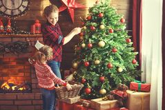 Happy family mother and child girl decorated Christmas tree Stock Photo