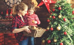 Happy family mother and child girl decorated Christmas tree. Happy family mother and child girl decorated a Christmas tree royalty free stock image