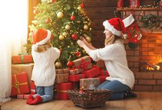 Happy family mother and child girl decorated Christmas tree Royalty Free Stock Images