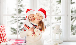 Happy family mother and child girl hugs at window at the winter Stock Image