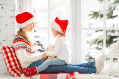 Happy family mother and child girl hugs at window at the winter Royalty Free Stock Photos