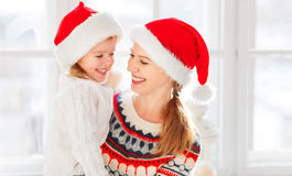 Happy family mother and child girl hugs at window at the winter Stock Photography